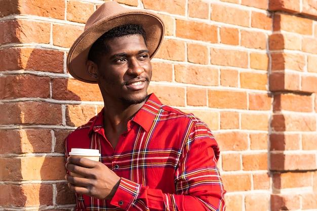Mann posiert beim halten einer tasse kaffee
