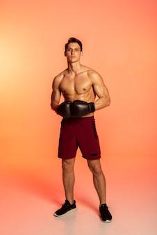 Mann posiert mit boxhandschuhen voller schuss