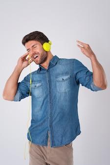 Mann posiert mit jeanshemd und kopfhörern