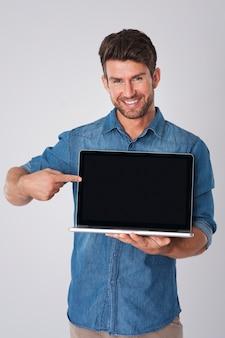 Mann posiert mit jeanshemd und laptop