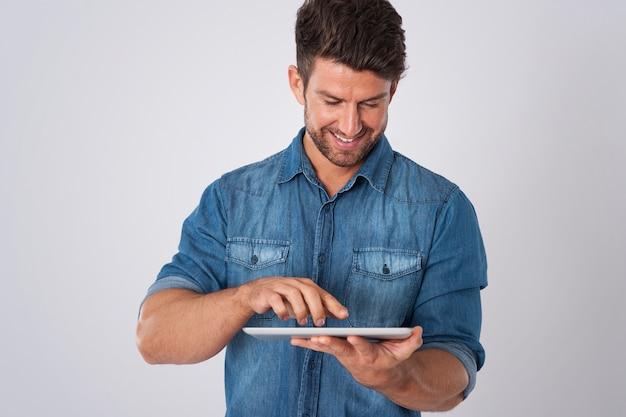 Mann posiert mit jeanshemd und tablette