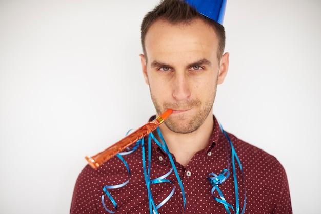 Mann posiert mit partyhorngebläse