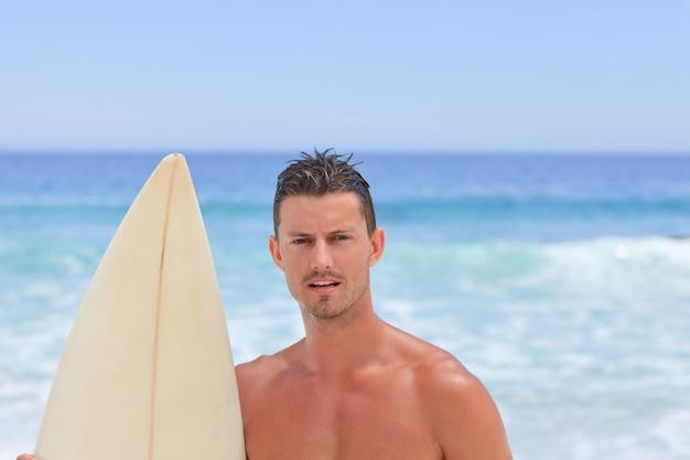 Mann posiert mit seinem surfbrett