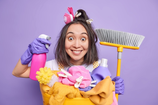Mann posiert mit spender und besenzubehör regelmäßige reinigung von hauswäschen wäsche verwendet chemische reinigungsmittel posiert im innenbereich