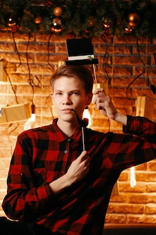 Mann posiert mit zylinderhut und pfeife fotokabine attribute gentleman in kariertem hemd auf backsteinmauer ...