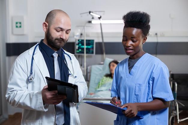 Mann praktiker diskutiert mit schwarzer assistentin in der krankenstation