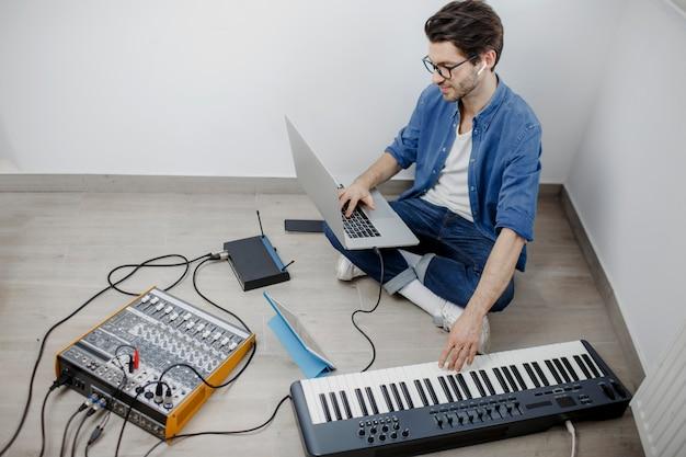 Mann produzieren elektronischen soundtrack oder track im projekt zu hause. männlicher musikarrangeur, der lied auf midi-klavier und audiogeräten im digitalen aufnahmestudio komponiert.