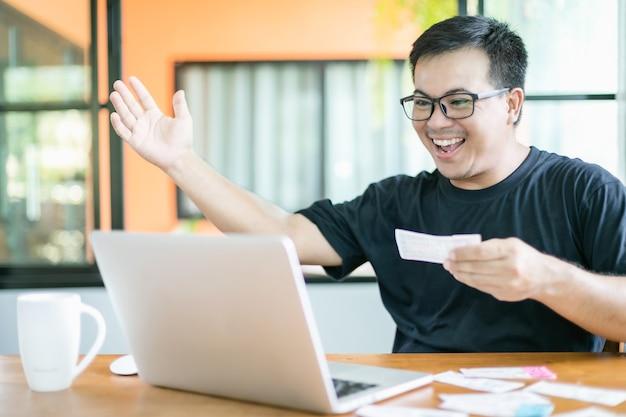 Mann prüft die ergebnisse der lotterie auf laptop und gewinnt