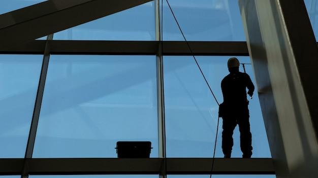 Mann putzt fenster an einem hochhaus