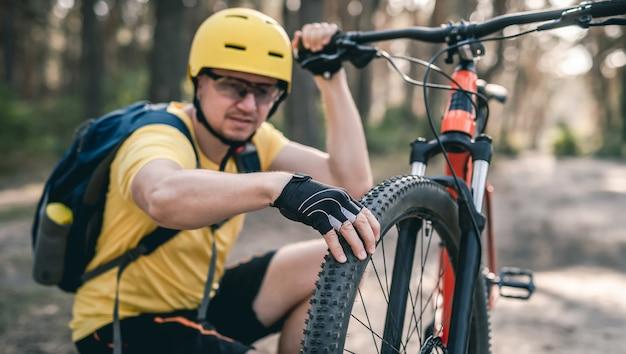 Mann-radfahrer, der den reifendruck des fahrrads vor der fahrt im wald überprüft