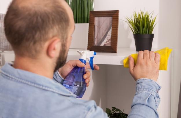 Mann räumt staub auf und hält sein haus sauber