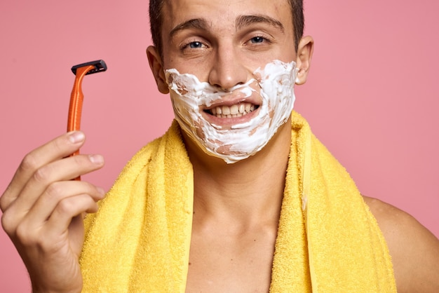 Mann rasiert sein gesicht mit einem rasiermesser mit rasierschaum