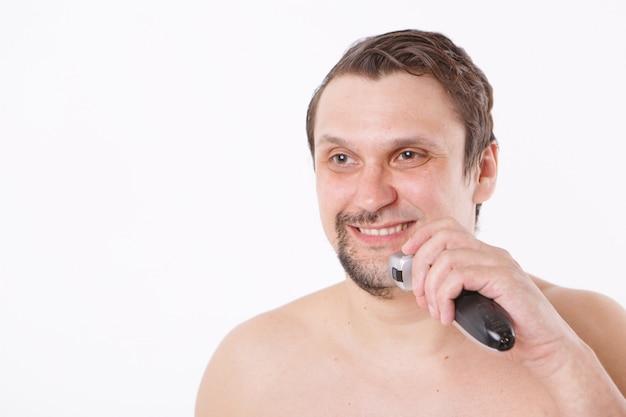 Mann rasiert seine stoppeln. mann reinigt seinen bart mit einem elektrorasierer. morgenbehandlungen im badezimmer.