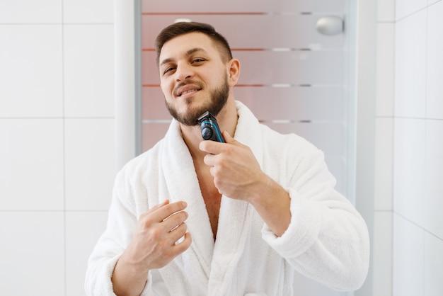 Mann rasiert seinen bart mit einem elektrorasierer