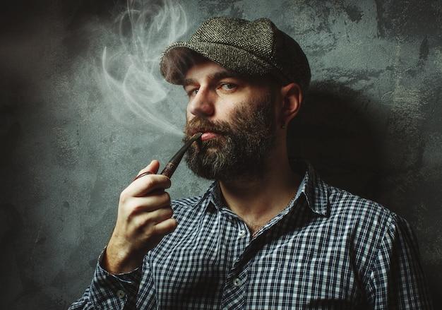 Mann raucht eine pfeife, die nahe der wand steht