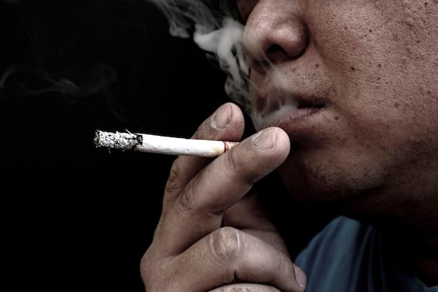 Mann raucht eine zigarette, bild einer zigarette in der hand mit rauch