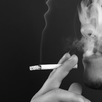 Mann raucht eine zigarette in weißem rauch auf einer dunkelheit.
