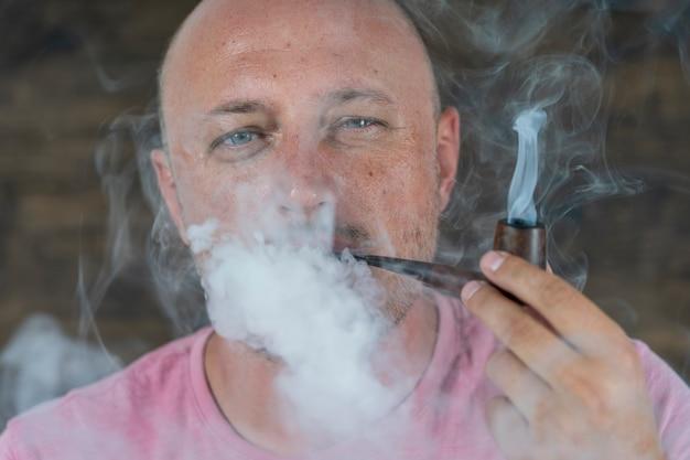 Mann raucht pfeife. porträt des mannes mittleren alters drinnen. schlechte gewohnheiten, sucht. ungesundes lebensstilkonzept. nahaufnahme