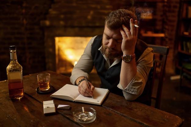 Mann raucht zigarette und schreibt in notizbuch, holztabler im hintergrund. kultur des tabakrauchens. männlicher raucher