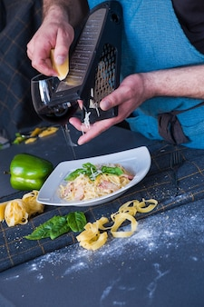 Mann reibt käse auf teigwaren mit speck, sahne, basilikum, parmesankäse auf weißer platte.