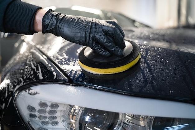 Mann reinigt autohaube mit kreisschwamm.