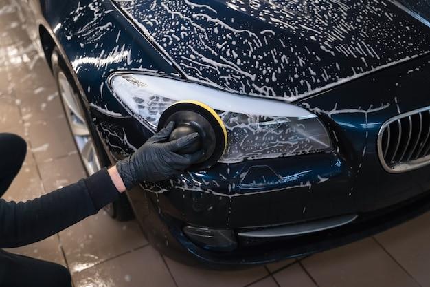 Mann reinigt autolampe mit kreisschwamm.