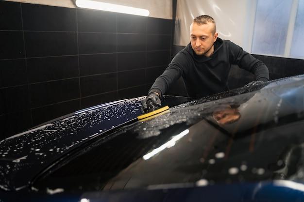 Mann reinigt heckscheibe des autos mit kreisschwamm.