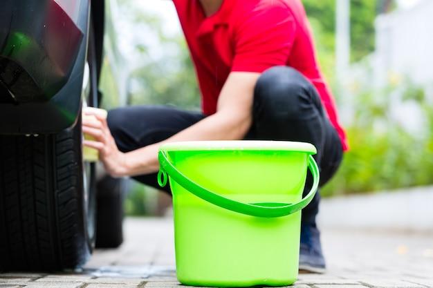 Mann reinigung felge während der autowäsche