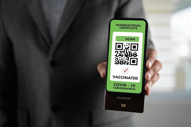 Mann reisen einwanderungspass karte, um eine impfbescheinigung gegen die covid-19 am flughafen zu zeigen