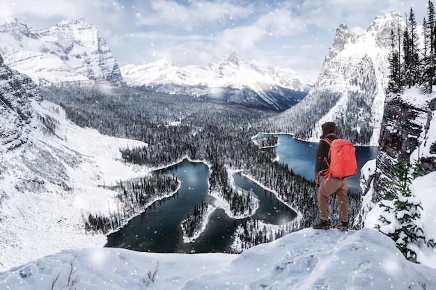 Mann reisender, der oben auf opabin plateau aussichtspunkt im schneesturm am yoho nationalpark steht