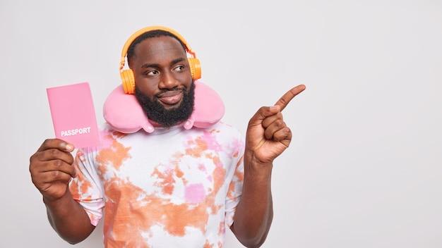 Mann reisender hört musik über kopfhörer, gekleidet in ausgewaschenem t-shirt verwendet reisekissen für die reise hält reisepass zeigt weg auf kopienraum