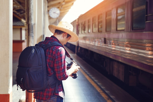 Mann-reisender mit fotokamera und rucksack stehen auf bahnhof