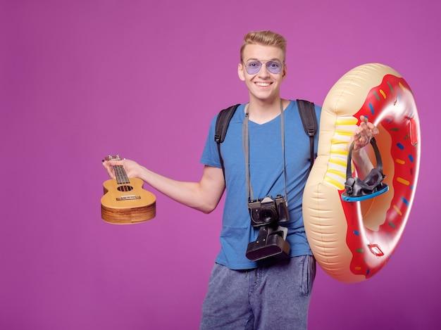 Mann reisender mit kamera, schwimmkreis und gitarrenukulele auf lila hintergrund