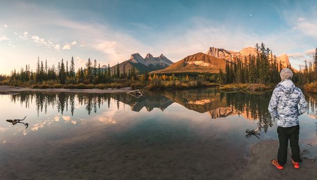 Mann reisender stehend genießen sie die landschaft der three sisters mountains reflexion über den fluss im herbst in canmore, kanada