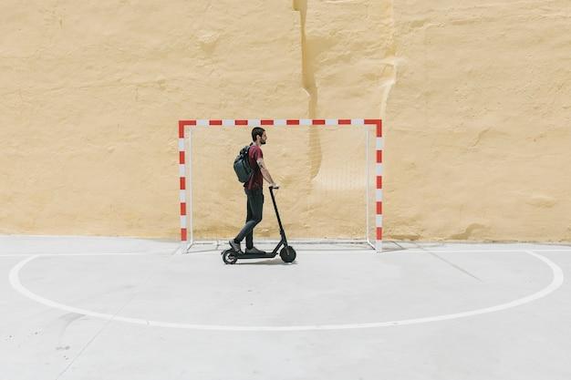 Mann reiten e-roller auf handballplatz