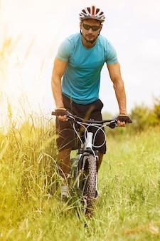 Mann reitet auf seinem fahrrad über die wiese