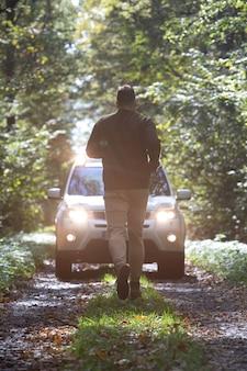 Mann rennt zum auto, das am waldweg mit eingeschalteten scheinwerfern steht
