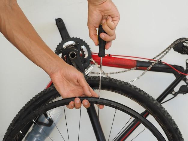 Mann repariert die speichen eines fahrradrades.