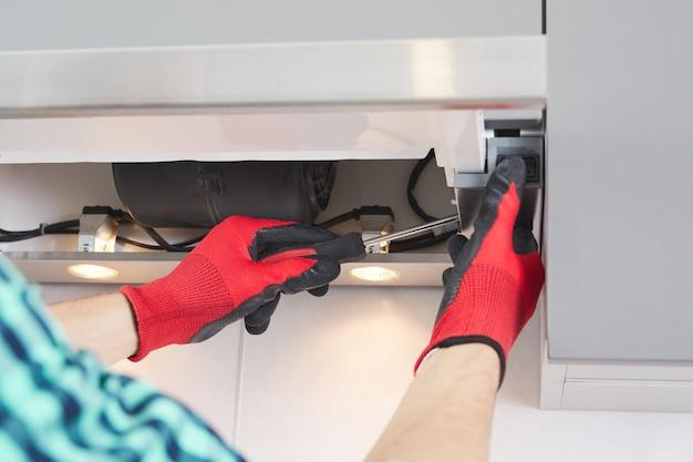 Mann repariert dunstabzugshaube in der küche. ersatzfilter in einer dunstabzugshaube.