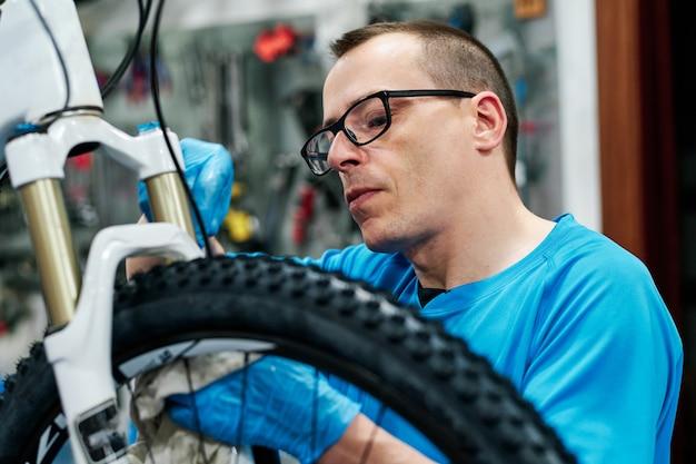 Mann repariert ein fahrrad in seiner kleinen werkstatt
