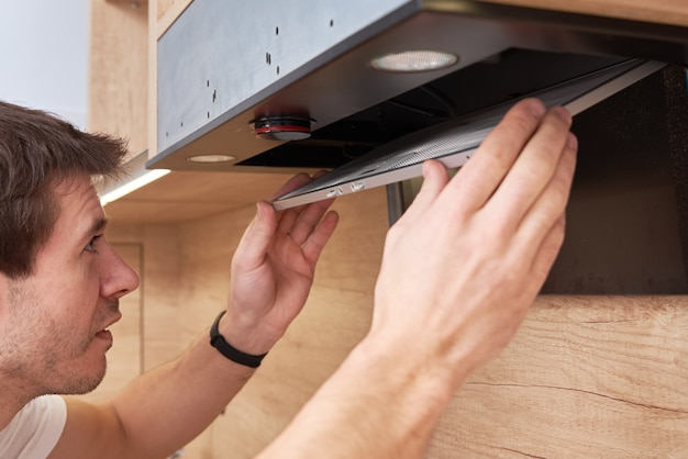 Mann repariert haube in der küche. ersatzfilter in der dunstabzugshaube