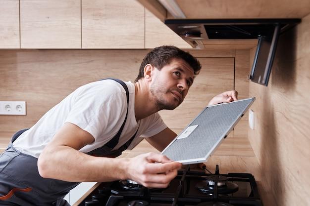 Mann repariert haube in der küche
