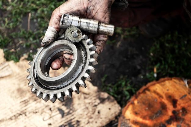 Mann repariert motor des traktors, landwirtschaftliche maschinerie. lager in schmutzigen händen.