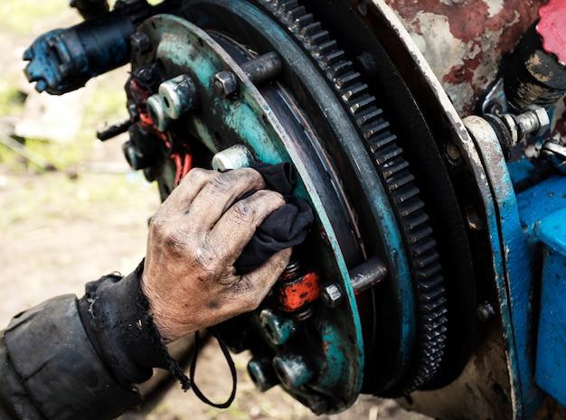 Mann repariert motor des traktors, landwirtschaftliche maschinerie. lager, zahnräder, nahaufnahme.