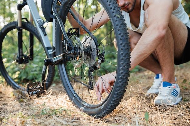 Mann repariert mountainbike im wald