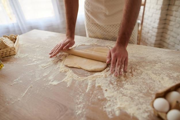 Mann rollt teig auf küchentisch aus.
