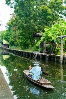 Mann ruderboot im kleinen kanal