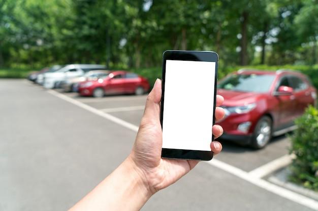Mann ruft auto mit handy app im parkplatz an