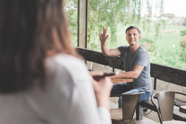 Mann ruft den kellner im café an