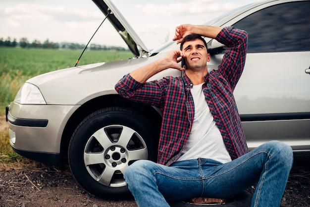 Mann ruft zum notdienst, kaputtes auto mit offener motorhaube
